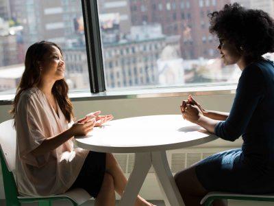 deux femmes en discussion dans la cafétaria d'une entreprise